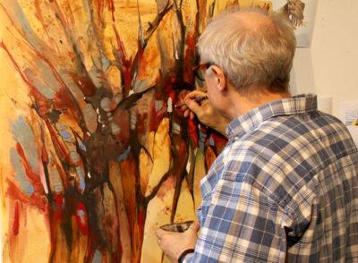 Henrik Skorá maler på et større maleri. Her ses et delbillede af et træ.